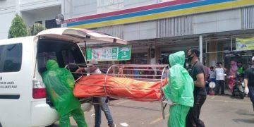 Petugas Dinas Pemakaman DKI Jakarta dengan menggunakan alat pelindung diri (APD) mengevakuasi jenazah meninggal dalam mobil di Jalan Raya Kebon Jeruk, Jakarta Barat, Jumat (10/4/2020).