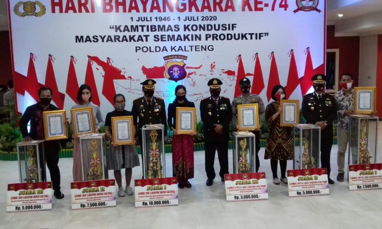 Dedet Anggota DPD KNPI Mura (Pojok Kiri Foto) Saat Menerima Piagam Penghargaan dan Tropi di Acara HUT Bhayangkara Polda Kalimantan Tengah