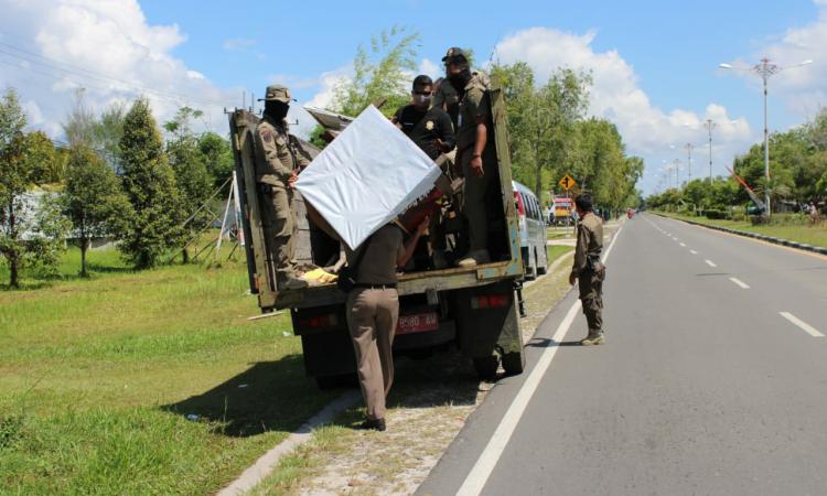 Anggota Satpol PP Kota Palangka Raya mengangkut gerobak PKL di Jalan Adonis Samad