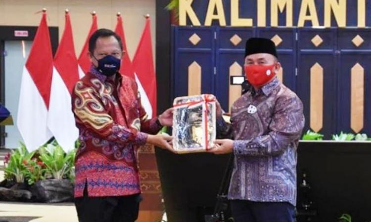 Mendagri Tito Karnavian menyerahkan buku panduan mesin ADM kepada Gubernur Kalteng Sugianto Sabran di Palangka Raya, Minggu (19/7/2020)