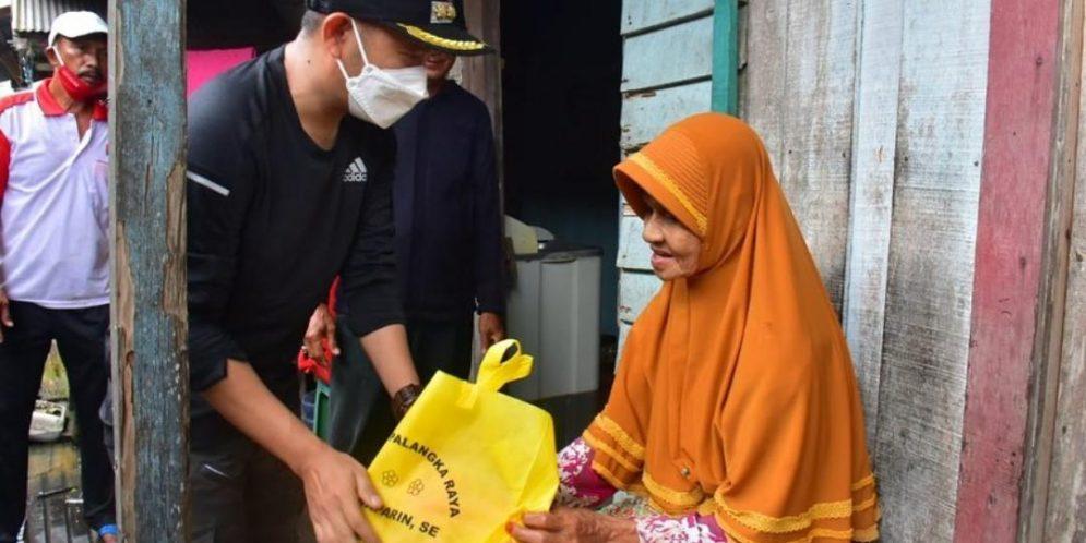 Wali Kota Palangka Raya Fairid Naparin saat memberikan bantuan bahan pangan kepada warga