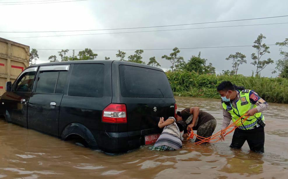 Personel Satlantas Polres Pulpis saat berupaya mengevakuasi mobil yang mogok
