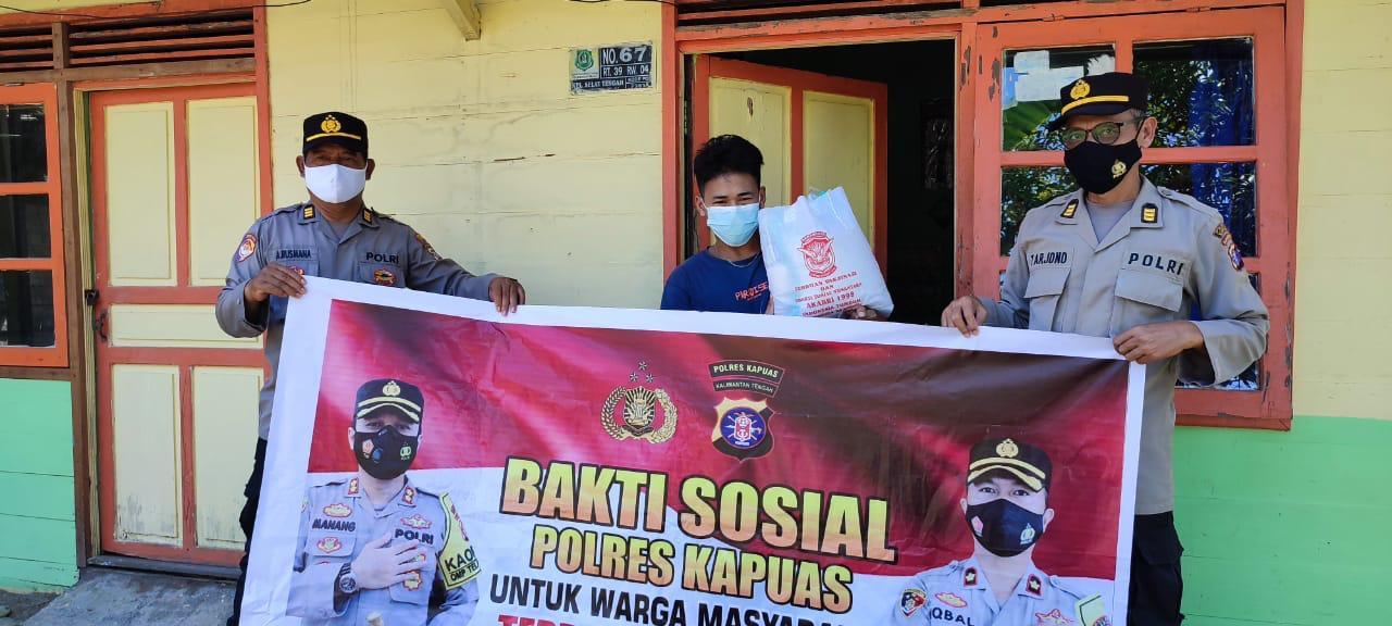 Perwira Polres Kapuas saat memberikan sembako kepada masyarakat yang kurang mampu